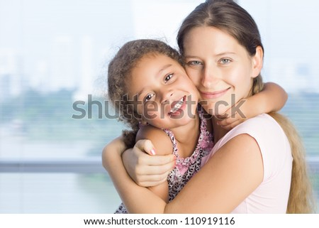 Affectionate mother and daughter looking at camera - stock photo