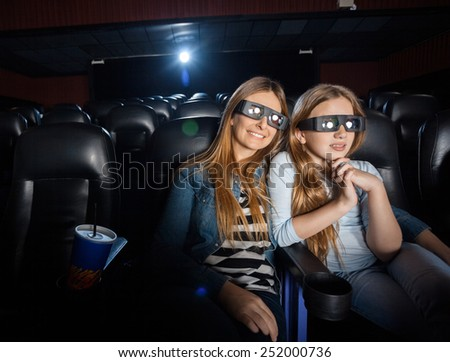 Affectionate mother and daughter watching 3D movie in cinema theater - stock photo