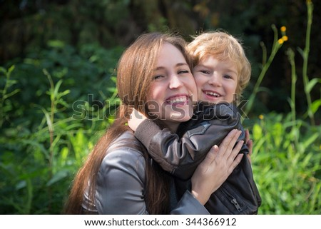 Affectionate mother and son hugging and enjoying in nature. - stock photo