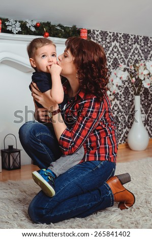 affectionate mother kisses her baby son on the cheek - stock photo