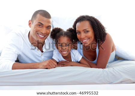 Affectionate parents and their daughter lying on a bed smiling at the camera - stock photo