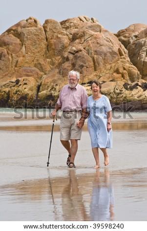 Affectionate senior couple walking on beach - stock photo