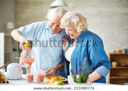 Affectionate seniors making fruit smoothie in the kitchen - stock photo