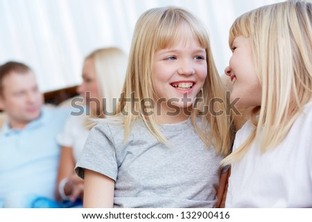 Affectionate twin sisters having fun in the foreground, their parents sitting behind - stock photo
