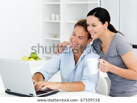 Affectionate woman looking at her boyfriend working on the laptop in the kitchen - stock photo