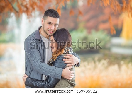 Affectionate young couple embracing in a park - stock photo