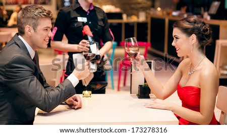 Affectionate young couple in exclusive restaurant toasting - stock photo