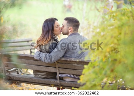 Affectionate young couple kissing in a park - stock photo