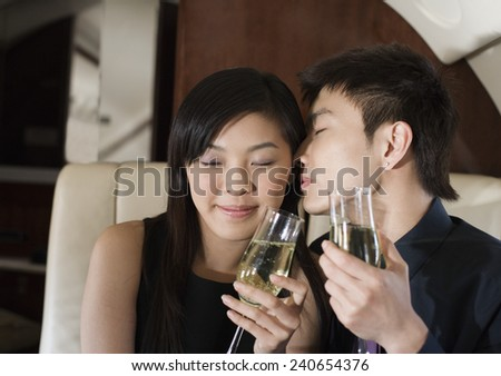 Affectionate Young Couple on Private Jet - stock photo