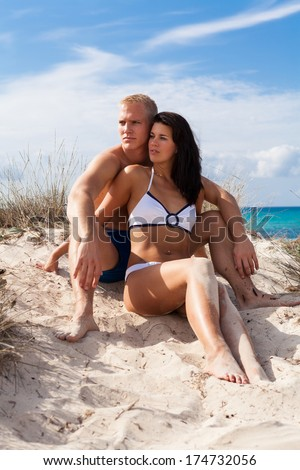 Affectionate young couple on the beach sitting in a close embrace on top of a sand dune overlooking the ocean in the summer sunshine - stock photo