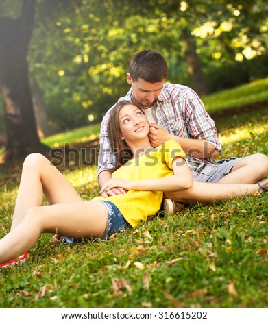 Affectionate young couple sitting in park - stock photo