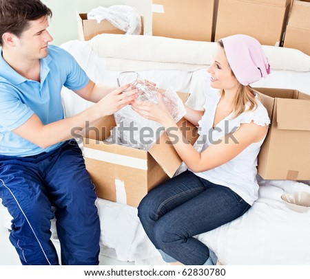 Affectionate young couple unpacking boxes with glasses in their new house