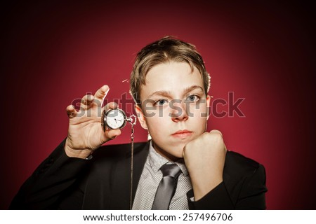 Affective teenage boy with watch showing time, isolated on red, concept