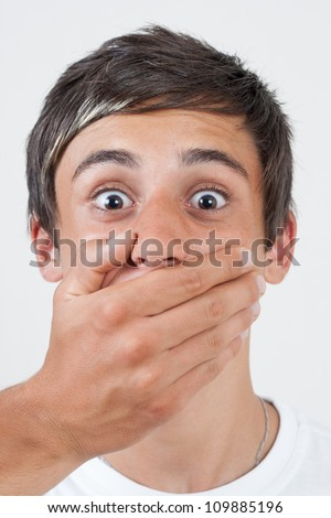 afraid swarthy victim man with hand covering his mouth - stock photo