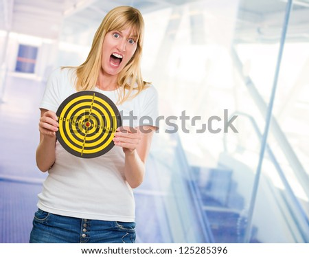 Afraid Woman Holding Dartboard, indoor - stock photo