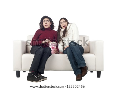 Afraid young females watching movie in living room sofa - stock photo