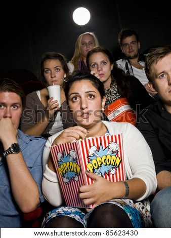 Afraid young woman at the movie theater with bag of popcorn - stock photo