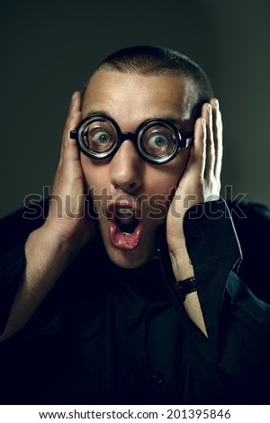 Afraided nerd guy holding his head and screaming - stock photo