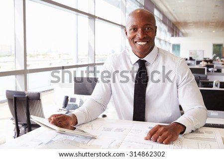 African American architect at work, smiling to camera - stock photo