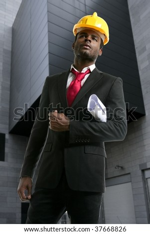 African american architect engineer with yellow hardhat and plans - stock photo
