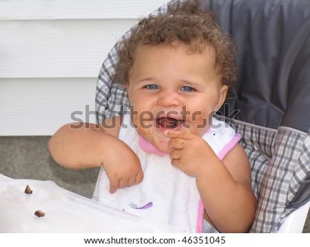 African American Beautiful Baby Blue Eyes Eating Food - stock photo