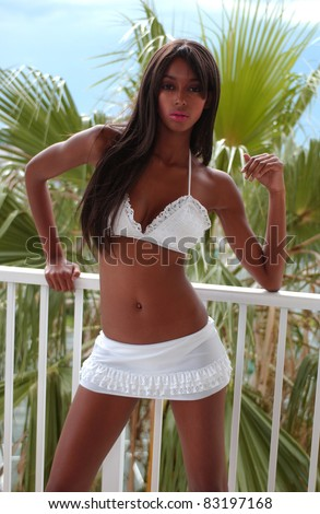 African American Bikini Girl on balcony with palm trees and blue sky on background - stock photo