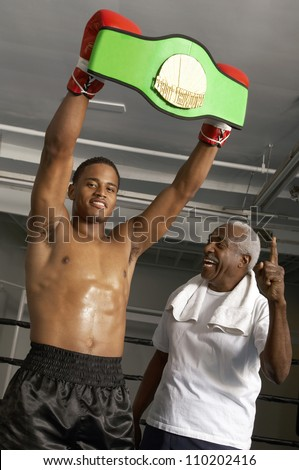 African American boxer holding championship belt with coach - stock photo