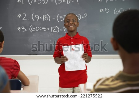 African American boy holding paper in front of class - stock photo