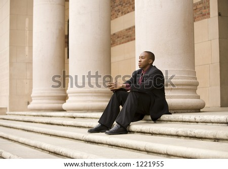African american business man sitting on steps in front of large pillars. - stock photo