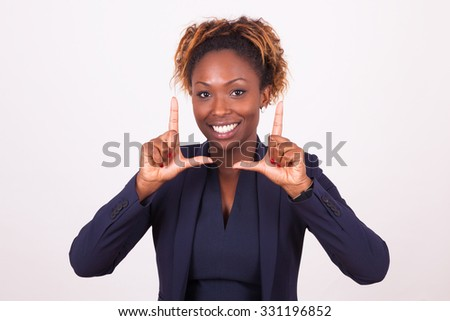 African American business woman making frame gesture with her hands, isolated on gray background - stock photo