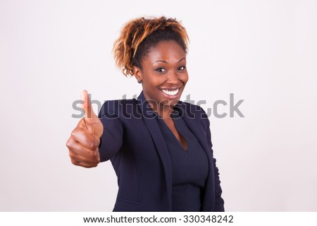 African American business woman making thumbs up gesture - stock photo