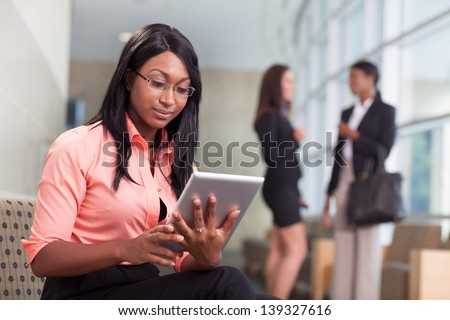 african-american business woman sitting in lobby, looking at tablet, two business women talking in background - stock photo