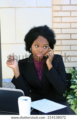 African American Business Woman Talking on the Phone Working on the Computer and Working on Paperwork - stock photo