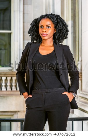 African American Business Woman working in New York. Wearing blazer, v neck undershirt, wristwatch, hands put in pockets, a black lady with braid hairstyle standing by office building, thinking  - stock photo