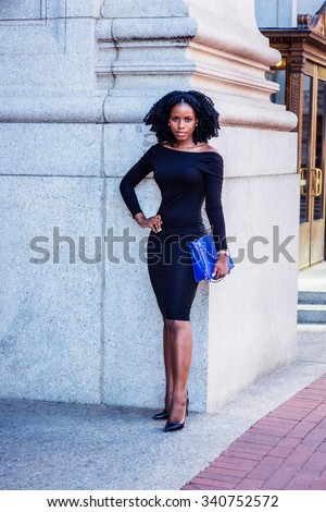 African American Business Woman working in New York. Wearing long sleeve, slim off shoulder dress, carrying blue bag, a black lady with braid hairstyle standing outside. Filtered look with purple tint - stock photo