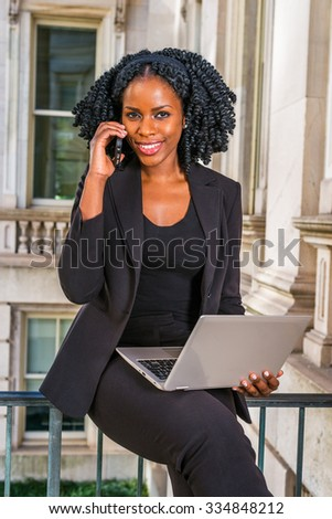 African American Business Woman working in New York. Young black lady with braid hairstyle sitting on railing in vintage style office building, smiling, working on laptop computer, making phone call.