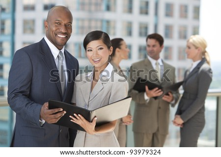 African American businessman and Chinese Asian businesswoman using a black folder with interracial group of business men & women team. - stock photo