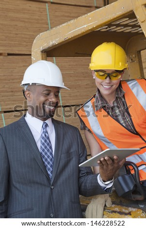 African American businessman and female industrial worker looking at tablet PC - stock photo