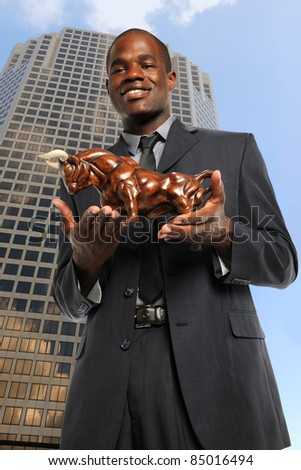 African American businessman holding bull with office building in background