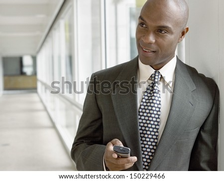 African American businessman holding mobile phone in office - stock photo