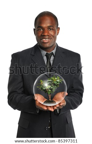 African American businessman holding tree inside crystal ball isolated over white background