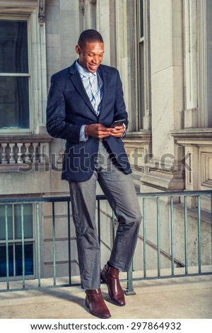 African American businessman in New York. Wearing black blazer, gray pants, brown leather shoes, a young guy standing in vintage style office, looking down, smiling, reading messages on mobile phone. - stock photo