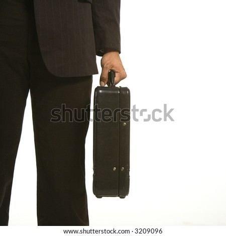 African American businessman in suit holding briefcase. - stock photo