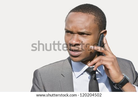 African American businessman looking away while talking on cell phone - stock photo