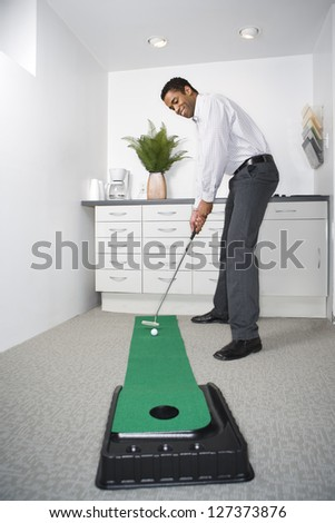 African american businessman playing mini golf in his office