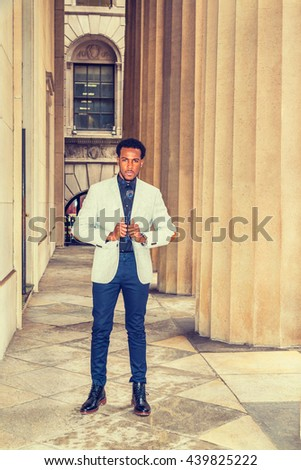 African American Businessman Semi-Formal fashion in New York, wearing gray blazer, blue pants, leather boot shoes, standing by columns outside office, looking forward. Instagram filtered effect. - stock photo