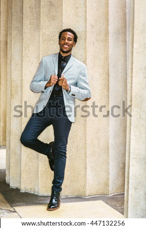 African American Businessman Semi-Formal Fashion in New York. Wearing gray blazer, unbuttoned,  blue pants, black leather boot shoes, guy standing against columns outside office, relaxing, thinking.  - stock photo