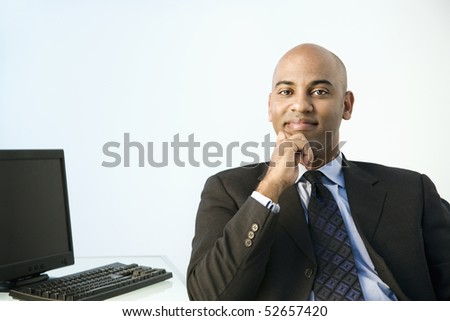 African American businessman sitting at office desk smiling. - stock photo