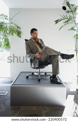 African American businessman sitting in chair on pedestal - stock photo