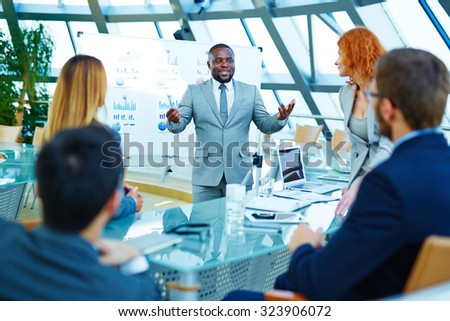 African-american businessman standing by whiteboard and voicing his opinion about data analysis to colleagues - stock photo